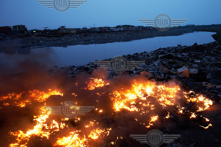 Monitor casings and other plastics burn along the edge of Agbogbloshie dump, which has become a dumping ground for computers and electronic waste from all over the developed world. Hundreds of tons of e-waste end up here every month. It is broken apart, and those components that can be sold on, are salvaged. Burning creates some of the most carcinogenic and toxic substances known, including polycyclic aromatic hydrocarbons, dioxins and furans, as well as releasing toxic metals such as lead, beryllium and cadmium. At theses burning sites concentrations of toxic metals have been found at over one hundred times the normal level.