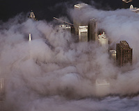 aerial photograph of the San Francisco, California financial district in the fog.  Portions of the Transamerica Pyramid, 101 California St, Spear Street towers and the Embarcadero Center