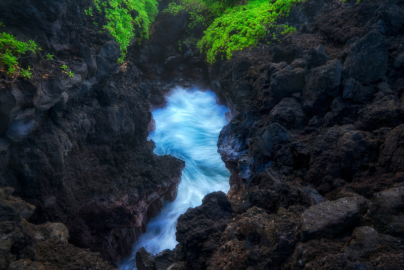 Rock opening in lava roack and incomming waves on Maui coast near Black sand Beach, Maui, Hawaii