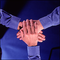 Three hands stacked on top of each other, viewed from above<br />