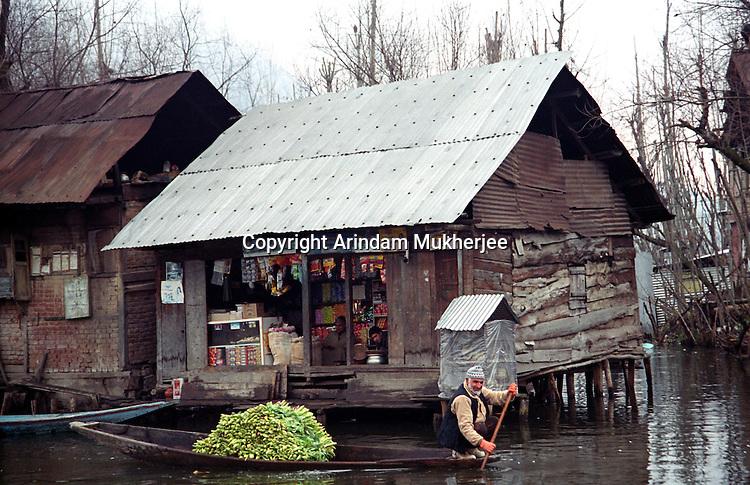 A kashmiri vegetable seller rows through Dal lake. Srinagar, Jammu & Kashmir, India. Arindam Mukherjee