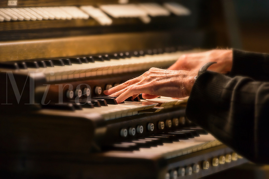 Hands playing a church organ.