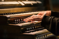 Hands playing a church organ.