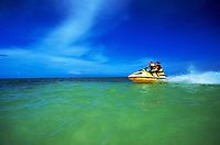 Dramatic view of a couple riding on a jet ski in green water undera bright blue sky.