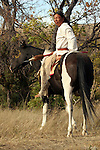 A Native American Indian man looking around while on a pinto horse