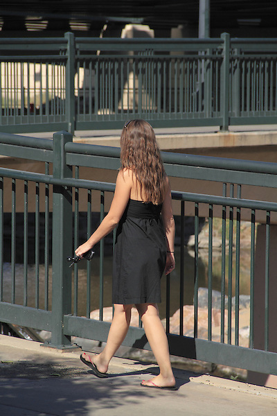Woman in black dress walking in Denver, Colorado. .  John offers private photo tours in Denver, Boulder and throughout Colorado. Year-round Colorado photo tours.