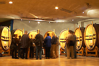 Wooden vats with aging wine in the cellar of Guigal in Ampuis. A group of visiting wine tasters in the tasting area. Blurred.  Domaine E Guigal, Ampuis, Cote Rotie, Rhone, France, Europe