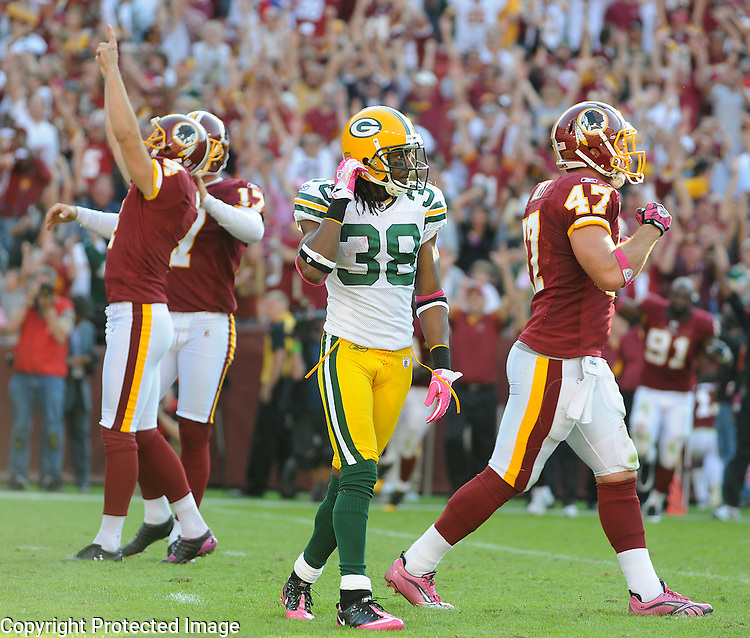 Green Bay Packers cornerback Tramon Williams, center, walks away as Washington Redskins kicker Graham Gano, left, holder Hunter Smith and Chris Cooley celebrate their game winning field goal during overtime of the game at FedEx Field in Landover, Md., on Oct. 10, 2010.