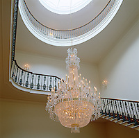 An elegant curved staircase snakes up this grand entrance hall which is lit by a crystal chandelier hanging from a central cupola