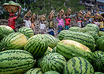 Unloading melons from boats using baskets balanced on heads by Zakirul Mazed