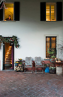 The windows of the guest house have been illuminated with tealights and the doorway decorated with spruce, winter berries and Christmas baubles