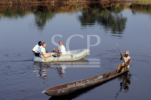 Zambia, Africa. Tourists in an inflatable dinghy greeting a man in a canoe marked 'Water Project Transport'; Chambeshi river.