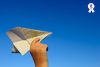 Hand holding paper plane on blue sky  (Licence this image exclusively with Getty: http://www.gettyimages.com/detail/103544607 )