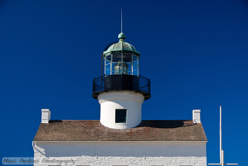A somewhat cropped view of Old Point Loma Light as seen from the east on a crystal clear blue sky winter's day.    The bright white painted brick building contrasts with the clear blue sky and black lantern room.  The flagpole (currently lacking a flag) can be seen to the right of the house.  The windows of the lighthouse are just barely visible at the bottom of the crop.  While I generally prefer pictures of lighthouses either tightly cropped or whole with their surroundings3, I find this view of the house to be strangely entrancing.  It seems to be standing alone in front of a clear blue sky; what's before it and behind it are unknown, open to the viewer to decide.