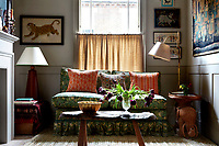 A comfortable two-seater sofa with contrasting cushions faces a rustic wooden coffee table in the living room