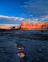 The reflection of sandstone rock formations in a shaded puddle. Lake Powell National Recreation Area, Utah.