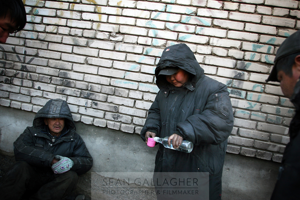 MONGOLIA. Ulaan Baatar. 8 a.m. The family use what money they have from collecting bottles to purchase cheap Russian Vodka which they drink in order to stave off the bitter cold that embraces Ulaan Baatar for large portions of the year.<br /> As the global financial crisis grips Asia, Mongolia is feeling the implications first hand as the country suffers from rising inflation pushing the price of food and fuel ever upwards. For the country's homeless, who live in sewers and abandoned garages in the capital and already face extreme discrimination and are denied access to basic health and social care, their lives are hanging in the balance. 2008