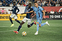 FOXBOROUGH, MA - SEPTEMBER 29: Wilfried Zahibo #23 of New England Revolution comes in to tackle Jesus Medina #19 of New York City FC during a game between New York City FC and New England Revolution at Gillettes Stadium on September 29, 2019 in Foxborough, Massachusetts.