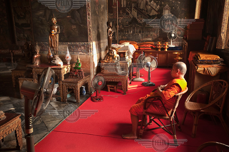A monk sits in a chair being cooled by fans in the main temple of Wat Suthat in Bangkok.