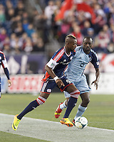 New England Revolution forward Dimitry Imbongo (92) dribbles as Sporting Kansas City midfielder Lawrence Olum (13) pressures. In the first game of two-game aggregate total goals Major League Soccer (MLS) Eastern Conference Semifinal series, New England Revolution (dark blue) vs Sporting Kansas City (light blue), 2-1, at Gillette Stadium on November 2, 2013.