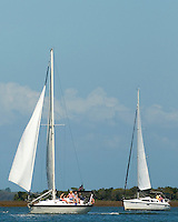 Vacationers sit on deck of a sailboat in Amelia Island, FL