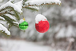 Snow-covered spruce tree decorated with Christmas ornaments