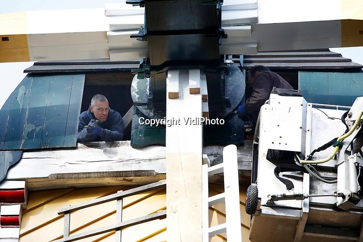 """Foto: VidiPhoto<br /> <br /> ARNHEM – Molenmakers van Verbij uit Hoogmade voorzien de gloednieuwe as van de Huizense molen (1665) in het Nederlands Openluchtmuseum (NOM) in Arnhem donderdag van een extra beschermlaag. De as en de wieken van de windkorenmolen, in 1916 een van de eerste gebouwen in het museum, waren aangetast door schimmel en zijn inmiddels vervangen door tropisch hardhout. Dat is minder gevoelig voor weersinvloeden dan eikenhout. Het lekkende dak moet nog wel gerestaureerd worden. Het NOM is vanwege de lockdown gesloten voor het publiek. Voor de bouwafdeling van het museum is dit de mooiste periode. """"Je kunt nu alles laten staan zonder dat je hinder veroorzaakt."""" Het Openluchtmuseum kampte jarenlang met achterstallig onderhoud. Dat is nu vrijwel volledig ingehaald."""