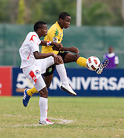 Oshane Jenkins (2) of Jamaica clears the ball away from Omar Browne (9) of Panama during the third place game of the CONCACAF Men's Under 17 Championship at Catherine Hall Stadium in Montego Bay, Jamaica. Panama defeated Jamaica, 1-0.