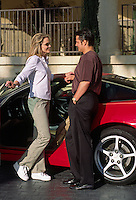 A MAN helps a WOMAN out of her RED CORVETTE AUTOMOBILE (MR)