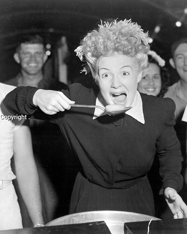 Betty Hutton visits chow halls with sailors and Marines in the Marshall Islands.  Peering over the screen star's shoulder is Virginia Carrol, dancer with the Hutton troupe.  December 1944. (Navy)<br /> Exact Date Shot Unknown<br /> NARA FILE #:  080-G-294122<br /> WAR & CONFLICT #:  756