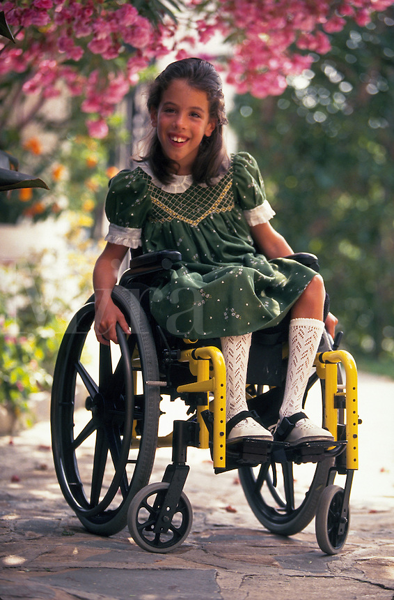 Portrait of a smiling young girl in a wheelchair..