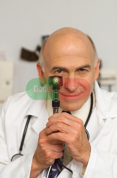 older, elder male doctor peering over otoscope, looking at camera