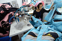 A female worker on production lines in a textile factory in Yixing city, in the Jiangsu Special Development Zone making clothes for New Balance. Much of the world's textile manufacture has moved to China due to relatively low labor rates and high productivity and those clothes are almost exclusively made by women between 6 and 25 years old..23 Sep 2006