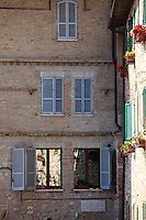 Assisi: A beautiful corner in the old small town, where two mirror windows reflect the partially shadowed and partially enlightened near wall. There are balconies that are adorned with red geranium plants, whose color is enhanced by the rose-colored background. As one can read on the plaque, this building was the house of Don Sigismondo Spagnoli.