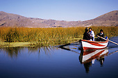 Lake Titicaca, Peru. Two men and a women in a red and white boat on the lake.