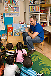 Education preschoool children ages 3-5 male teacher reading pictrue book to group of children seated on rug vertical