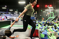 Victoria Hernandez of Rogers (center) and Aiden Almeida, 3, (left) takes a running start to jump into a ball pit, Friday, July 16, 2021 at Defy Rogers in Rogers. Kids played on trampolines, trapezes and in foam pits at the trampoline and extreme airsports park. Check out nwaonline.com/210717Daily/ for today's photo gallery. <br /> (NWA Democrat-Gazette/Charlie Kaijo)