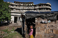 A girl stands at the entrance to a cinema shack (dvd covers display what is playing) built in the grounds of the former Grand Hotel building. Once a luxury destination for the wealthy and the continent's biggest hotel, the building is now a concrete shell and home to about 6,000 squatters. Those unable to occupy one of the rooms sleep in the corridors, basements and even on the roof of the building.