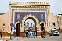 Fes, Morocco.  Young Women Passing through the Bab Boujeloud, Entrance to Fes El-Bali, the Old City.  The minaret of the Bou Inania medersa is in the background.