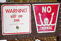 Warning signs by river's edge.