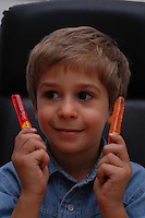 Cibi pericolosi. Bambino con lecca lecca che contiene un meccanismo al mercurio per farlo illuminare..Hazardous foods. Child with lollipops that contains a mechanism with mercury to illuminate it...
