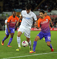 (L-R) Jack Cork of Swansea City is challenged by Jesus Navas of Manchester City during the EFL Cup Third Round match between Swansea City and Manchester City at The Liberty Stadium in Swansea, Wales, UK. Wednesday 21 September.