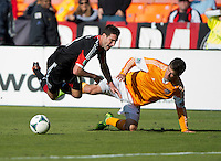 Bobby Boswell (32) of the Houston Dynamo fouls Chris Pontius (13) of D.C. United during a Major League Soccer game at RFK Stadium in Washington, DC. D.C. United vs. Houston Dynamo, 2-1.