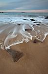 Waves swirl around the rocks at Sand Beach in winter in Acadia National Park, Mount Desert Island, Maine, USA