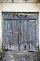 A white heart pierced by Cupid's arrow has been chalked on to one of a pair of dilapidated garage doors