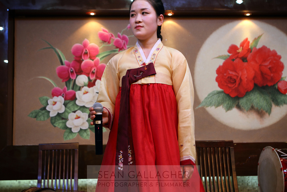 China. Jilin Province. A North Korean woman performs for customers in a restaurant in the town of Yanji, close to the border with North Korea. The town is part of the Korean Autonomous Prefecture in the north-east of the country. 2011