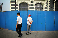"""CHINA. Beijing. A man peers through a fence, trying to catch a glimpse of the new Qianmen shopping district. In recent years construction has boomed in Beijing as a result of the country's widespread economic growth and the awarding of the 2008 Summer Olympics to the city. For Beijing's residents however, it seems as their city is continually under construction with old neighborhoods regularly being razed and new apartments, office blocks and sports venues appearing in their place. A new Beijing has been promised to the people to act as a showcase to the world for the 'new' China. Beijing's residents have been waiting for this promised change for years and are still waiting, asking the question """"Where's the new Beijing?!"""". 2008"""