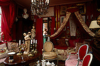 A daybed complete with corona and drapes dominates one end of this red sitting room