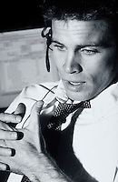 A young executive man talking on a phone headset.