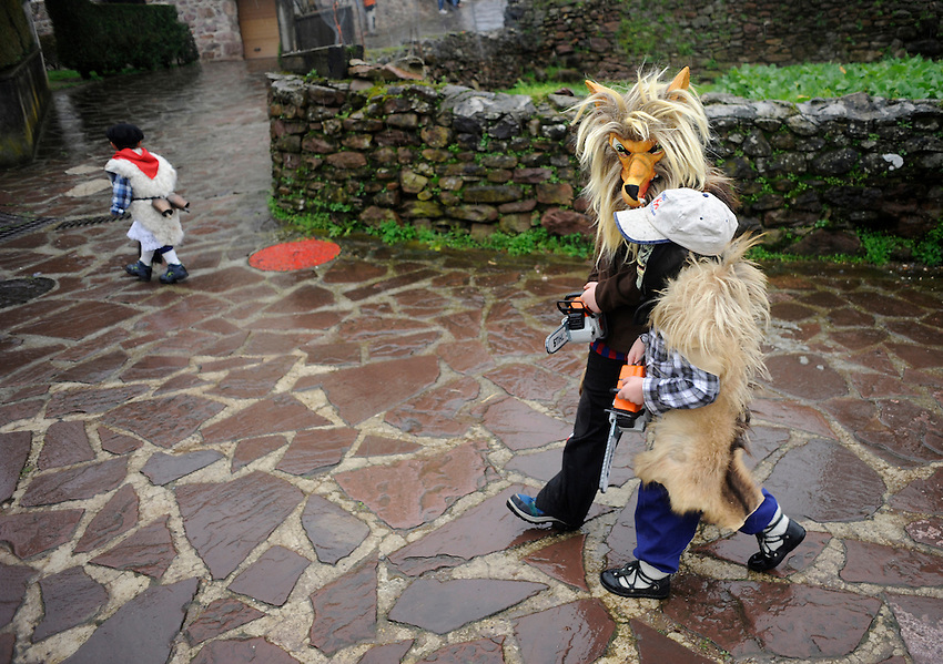 Masked children perform during an ancienta carnival on January 27, 2014 at the village of Ituren, Basque Country. Joaldun groups perform an ancient traditional carnival at the villages of Ituren and Zubieta during two days, carrying sheep furs and big cowbells in their backs and making sound them in order to wake up the earth, to ask for a good new year, a good harvest and also to keep away the bad spirits. (Ander Gillenea / Bostok Photo)